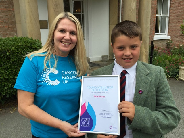 Louise Aubrey from Cancer Research presents Tom Evans with his Flame of Hope award.